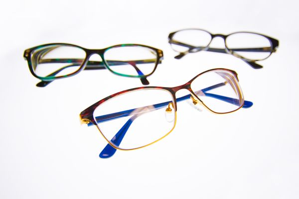 photo of three pairs of glasses on white background